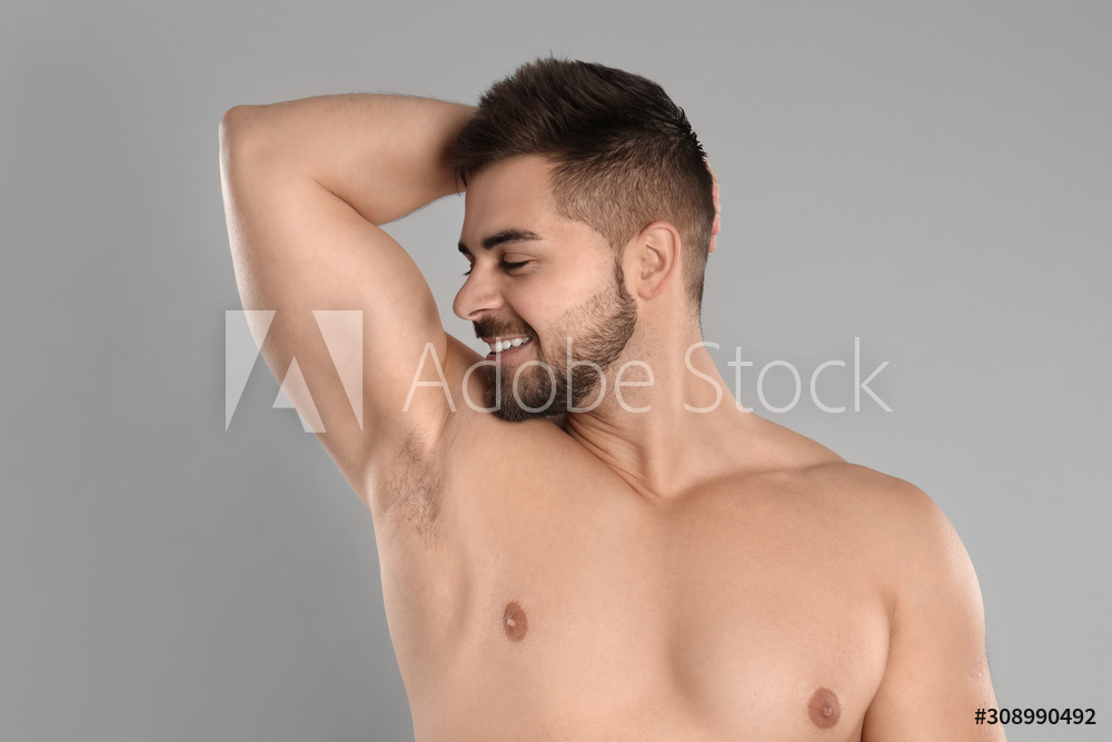 Young man showing hairless armpit after epilation procedure on grey background