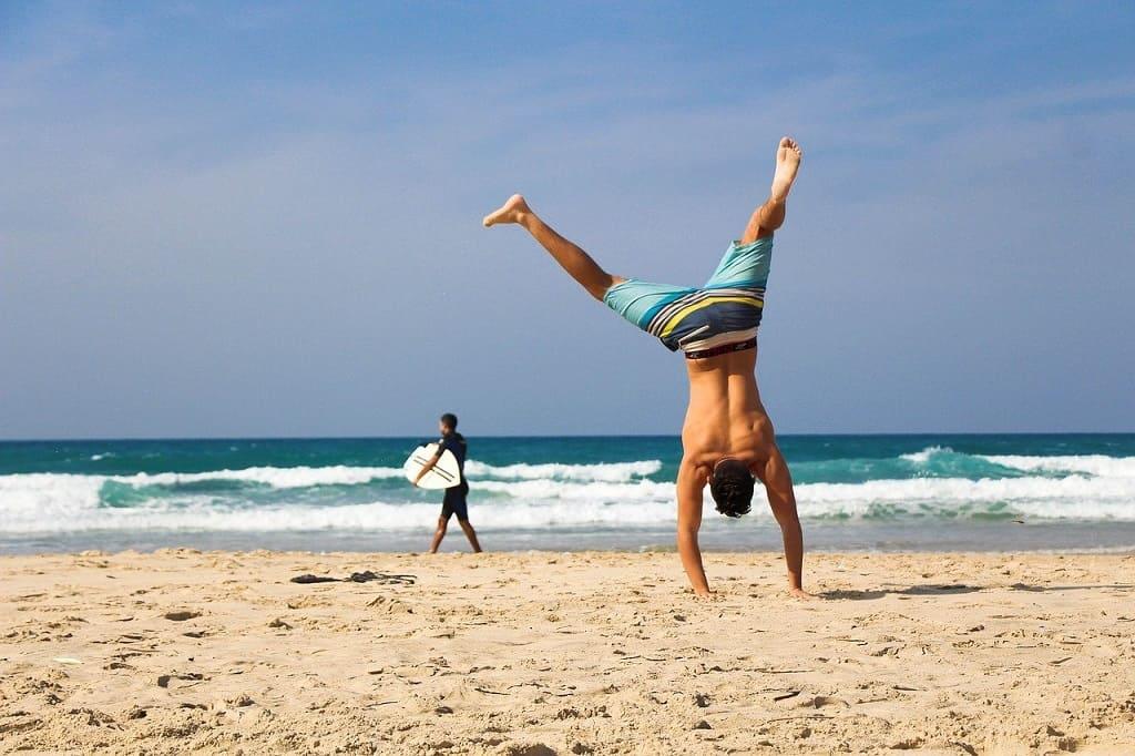 ビーチで逆立ちをする男性